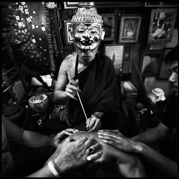 A tattoo master applying a tattoo to a devotee