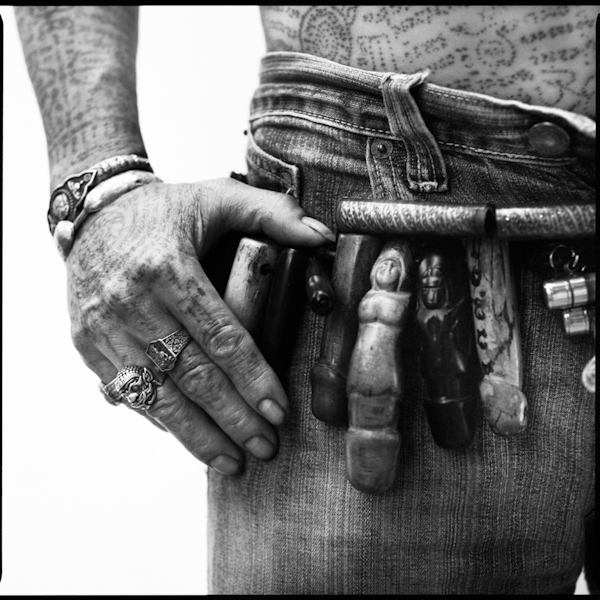 Details of a man's tattoos on his hand and arms - the amulets hanging from his belt are known as palat kik