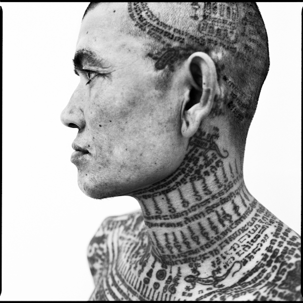 Details of tattoos on a man's neck and head