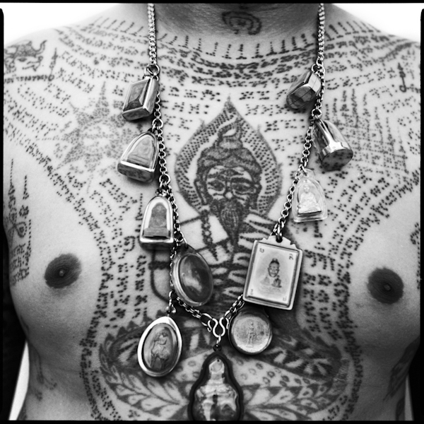 Tattoo details and amulets on a man's chest