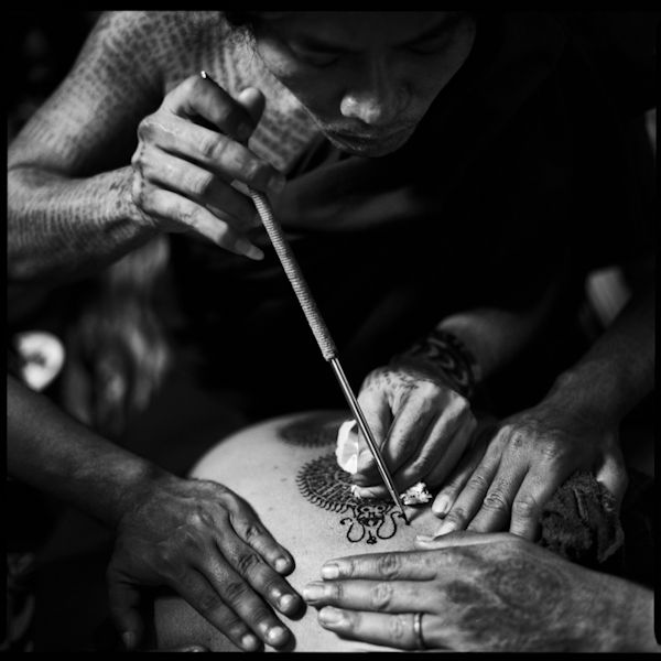 A bangkok tattoo master applies a tattoo
