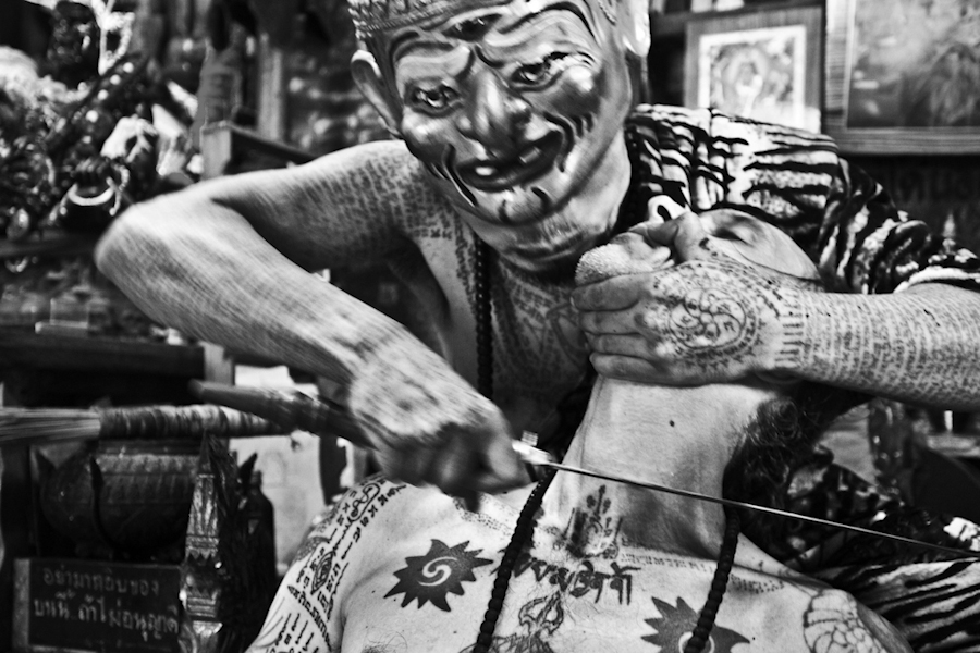 "A tattoo master in Bangkok tests the ""power"" of a tattoo by running a sword blade accross a devotee's neck."